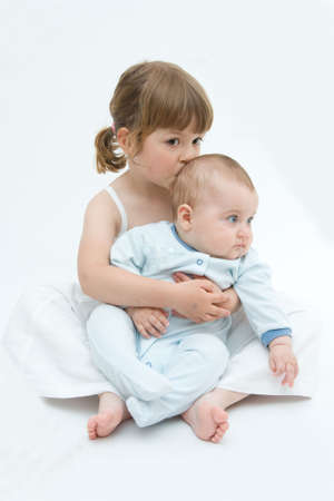 little sister hugging her tiny baby brother, on white background Stock Photo