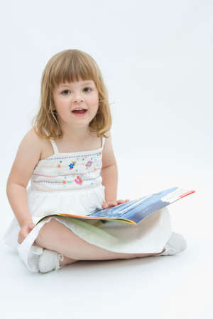 little girl reading fairy tales on white background photo