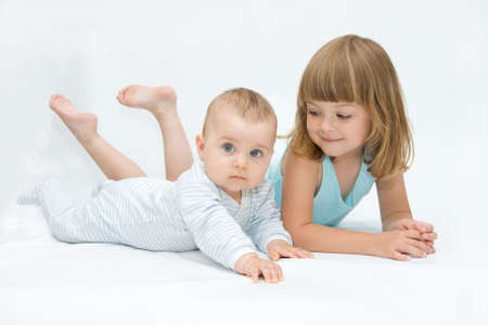 little brother and sister playing together, on white