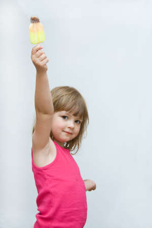 little, pretty girl licking fruity ice cream, on white background