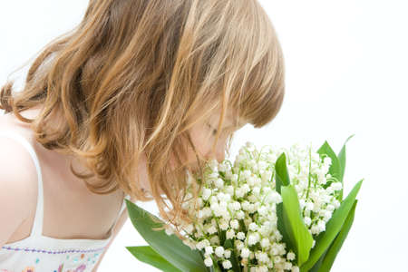 little, pretty girl smelling bunch of lilies of the valley on white background photo