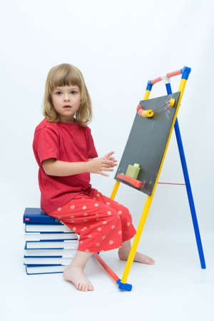 little girl sitting on a pile of books and drawing on blackboard Stock Photo - 3437716