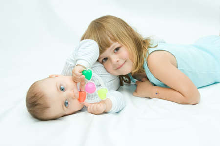 sister and brother: little brother and sister playing together, on white