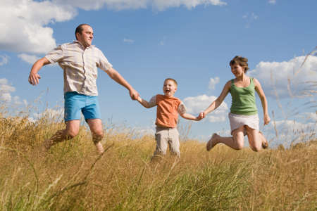 happy family jumping together on a summer day photo