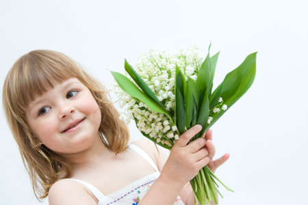 little, pretty girl holding bunch of lilies of the valley on white background photo