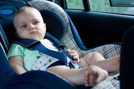 little baby sitting in safety car seat