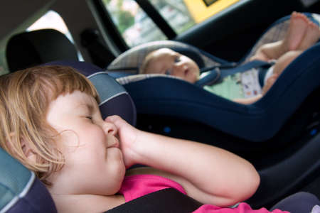 car seat: little  and girl sitting in safety car seat