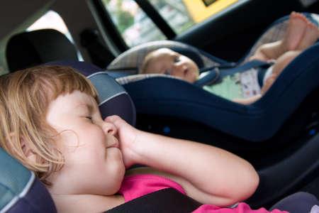 asiento coche: poco y ni�as sentados en asiento del coche de seguridad Foto de archivo