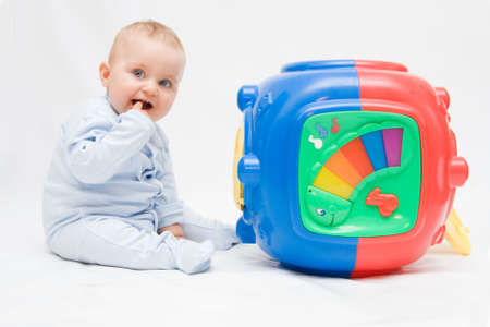 cute baby boy playing with colorful toys photo