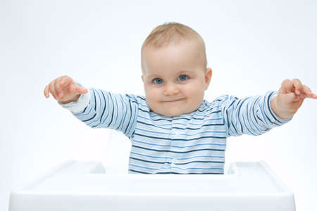 making faces: cute baby ragazzo seduto in una sedia alta e facendo facce Archivio Fotografico