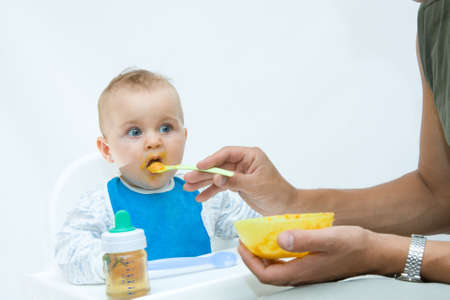 man feeding baby with a spoon, on bright background Stock Photo - 3529418