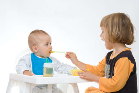 little girl encouraging her baby brother to eat Stock Photo - 3529421