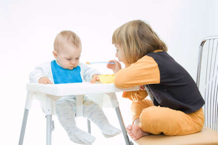 little girl encouraging her baby brother to eat Stock Photo - 3529425