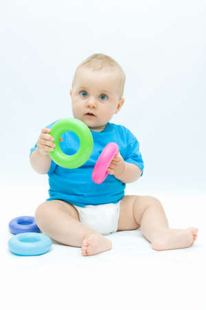 cute baby boy playing with colorful toys