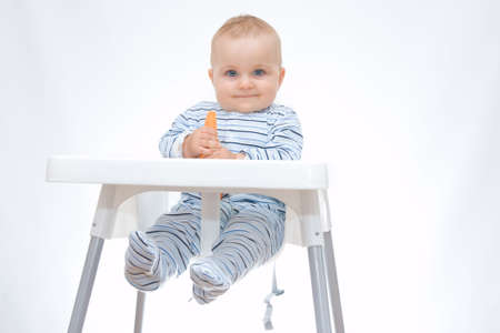 little, cute baby boy eating fresh carrot, on white