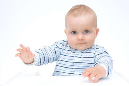 making faces: Cute Baby ragazzo seduto in un seggiolone e facendo fronte
