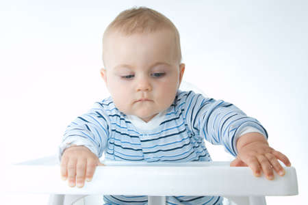 cute baby boy sitting in a high chair and making faces photo