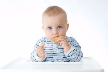 cute baby boy eating biscuits, on white