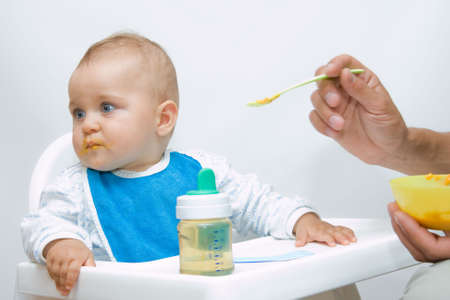 man feeding baby with a spoon, on bright background