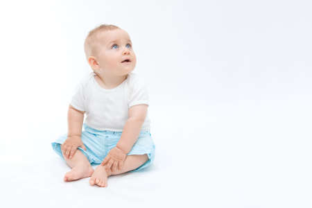 laughing baby: cute laughing baby boy sitting on white background