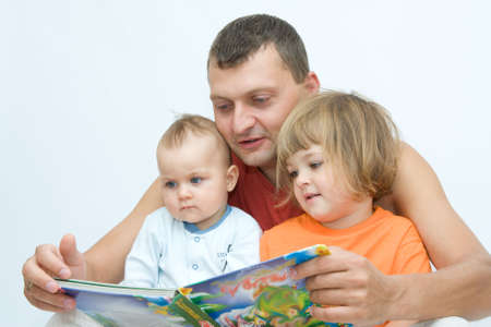 young father reading fairy tale to children photo