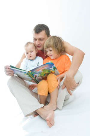 young father reading fairy tale to children