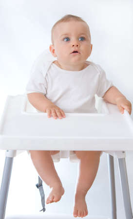 little, cute baby boy sitting in high chair, on white