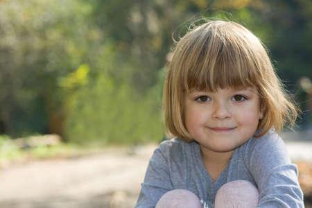 portrait of a pretty little girl in autumn scenery