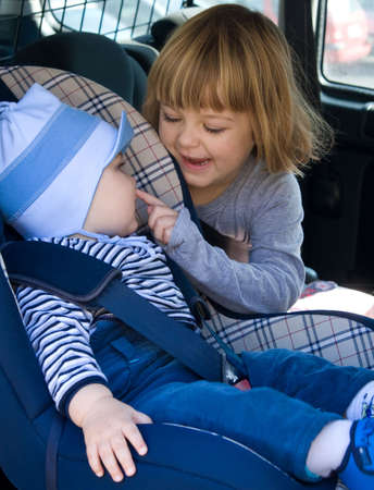 boy and little girl laughing in car backseat Stock Photo