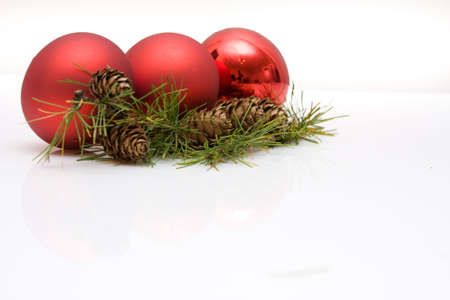 green conifer with cones, red baubles and white copy space photo