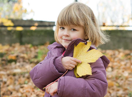 little, cute girl on an autumn walk 写真素材