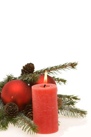 Christmas composition of conifer, red baubles and candle photo