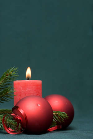 Christmas composition of conifer, red baubles and candle Stock Photo
