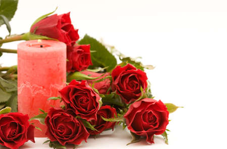 red roses and candle, on white background