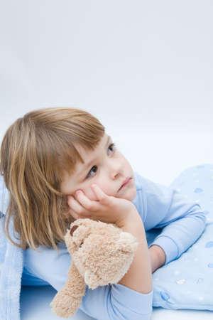 little, sleepless, girl lying in bed with teddy bear
