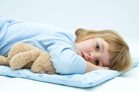 ni�os enfermos: poco, dormir, ni�a en la cama con el osito de peluche Foto de archivo