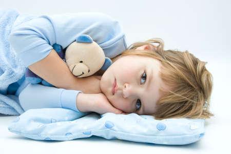 enfant malade: peu, le sommeil, les jeunes filles couch�es dans le lit des ours en peluche