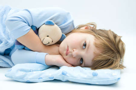 ni�os tristes: poco, dormir, ni�a en la cama con el osito de peluche Foto de archivo