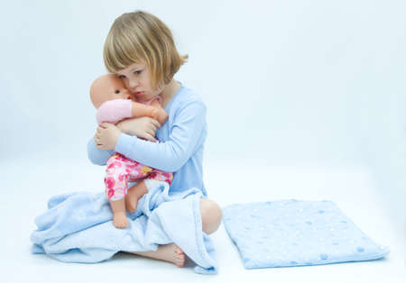 girl in bed, hugging her baby doll