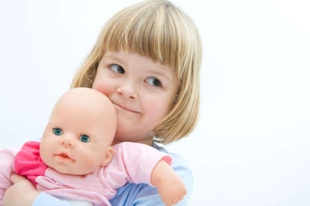 little girl hugging her baby doll and smiling