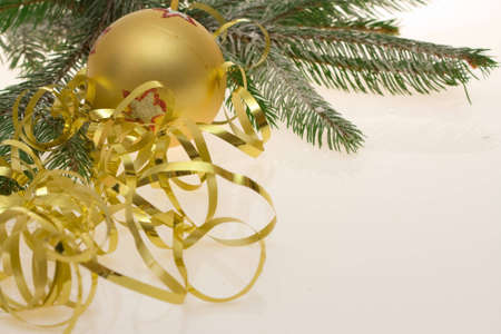 golden bauble, ribbon and spruce twigs on light background photo