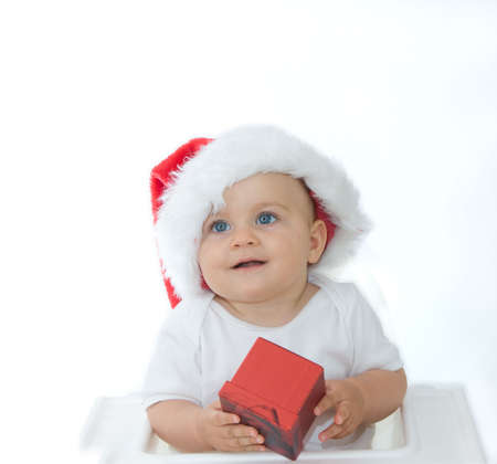 little, cute baby boy wearing Christmas hat, on white photo