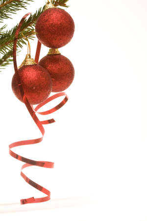 three red Christmas balls and spiral ribbon, on white photo