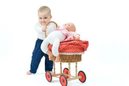 little baby boy pushing toy pram, on white