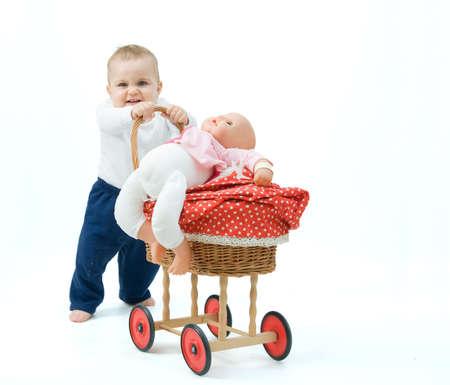 little baby boy pushing toy pram, on white