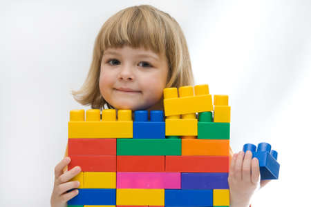 little girl playing with colorful blocks, on white Stock Photo