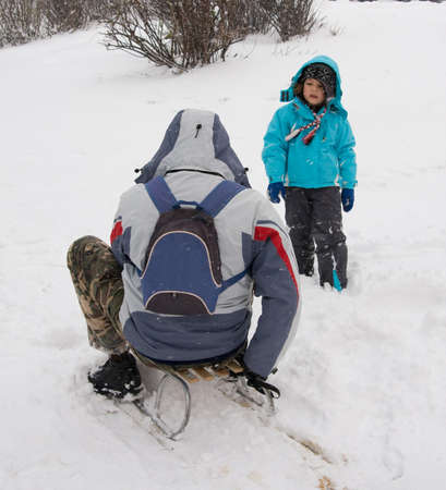 sledging people: kid sledging while it is snowing and cold Stock Photo