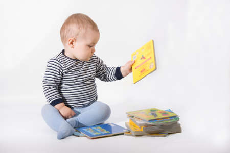 baby boy playing with books, on white