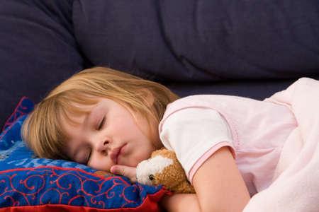 little, cute girl sleeping on blue pillow Stock Photo