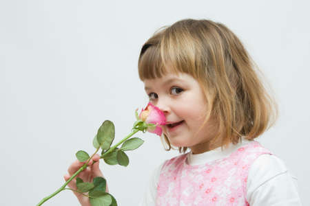 admire: little, pretty girl smelling beautiful pink rose Stock Photo